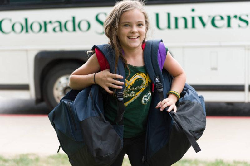 Young volunteer delivering backpacks